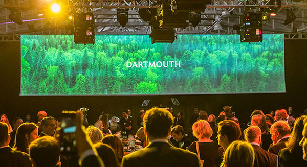 A crowd stands in front of a large screen showing green trees and the Dartmouth wordmark.