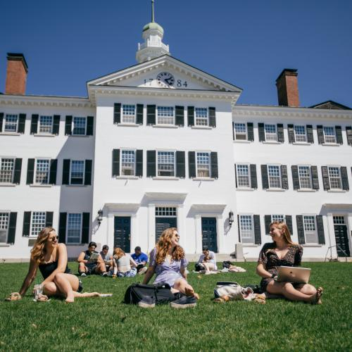 Women sitting on the grass in front of Dartmouth Hall