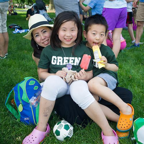 A woman and two children wearing Dartmouth shirts pose for a picture.