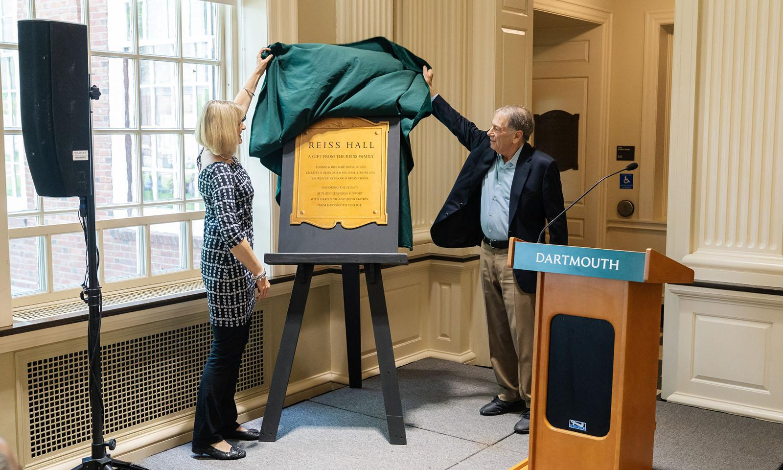 Two people unveil a sign on an easel