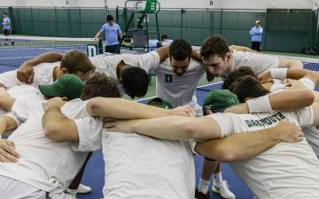 men's tennis team huddled on the court