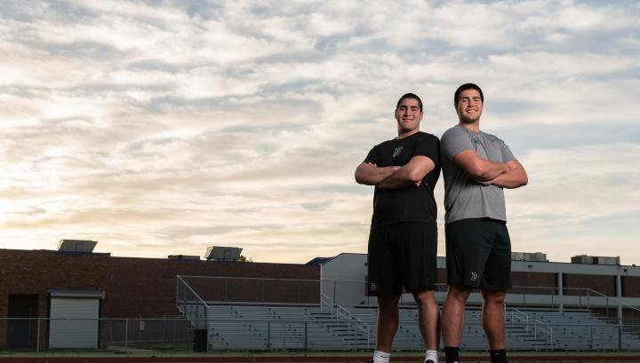 John Flores '22 and Michael Flores '23 standing on a football field