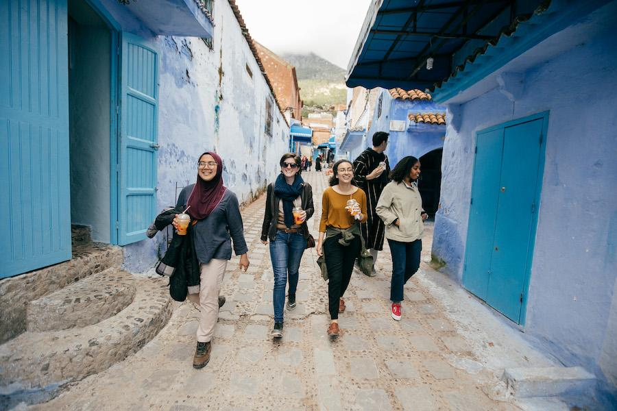 Four students walk down a colorful lane in Morocco.