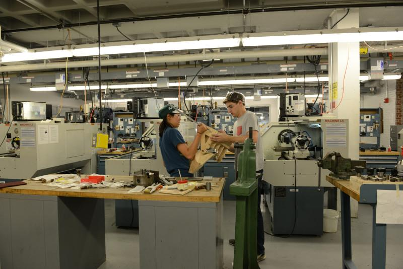 Dartmouth students assemble mechanical linkage prototype in the Thayer School of Engineering Machine Shop.