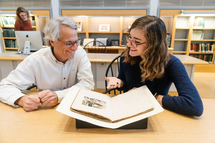 A man and woman look at a rare book together in a library.